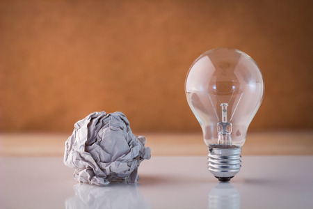 crumpled paper ball: bulb and trash paper ball with brown background Business Ideas Concept