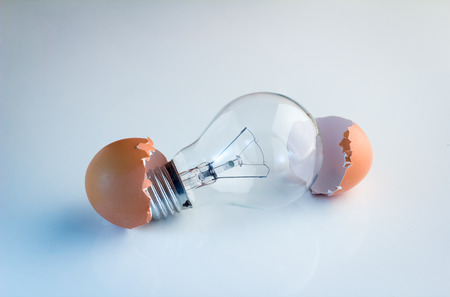 Innovation Bright Ideas Light Bulb Hatching From Egg Shell on white floor Banque d'images