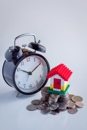 mortage: house model withalarm clock on Pile of  coins. Conception of growth of mortage Stock Photo