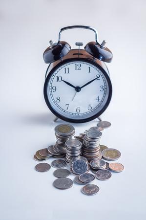 cronologia: Alarma de pie con la torre de monedas en el cuadro blanco, el concepto de gestión de dinero