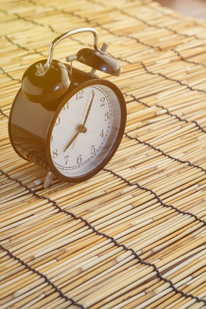 bamboo mat: morning time concept with alarm clock on bamboo mat