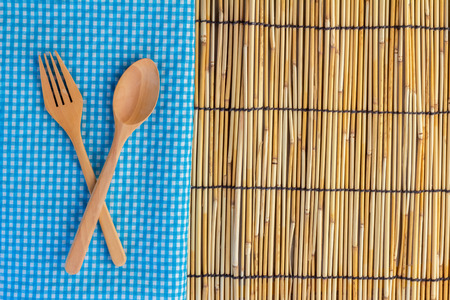 cooking implement: Wooden kitchen spoon on a fresh checkered rustic blue and white napkin on a bamboo mat counter with copyspace Stock Photo
