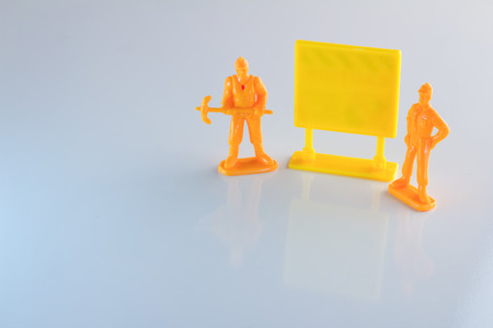temporarily: workers toy and blank yellow signage business concept.jpg