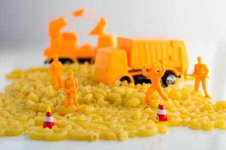 workmen: uncooked pasta and set of workmen on a white background food industry concept