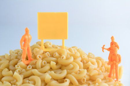 workmen: uncooked pasta and set of workmen on white table Stock Photo
