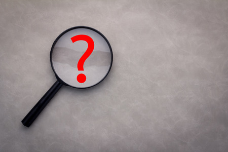 orthographic symbol: question mark under a magnifying glass with grey background