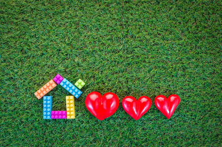 man made structure: home sweet home concept with home model and three red hearts on green grass field with copy-space for your text