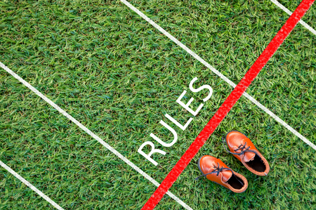 breaking the rules: brown shoes standing on the grass field with the word rules  The concept of rules