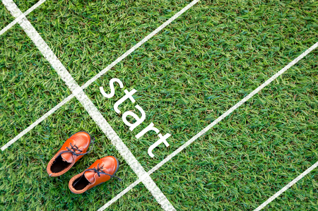 brown shoes standing on the grass field with the word start  The concept of start Stock Photo