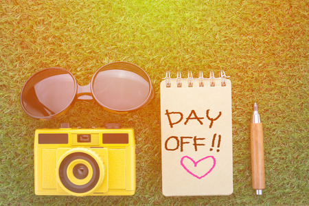 day off concept with sun glasses notebook camera and sharp pencil on grass texture view from top Archivio Fotografico