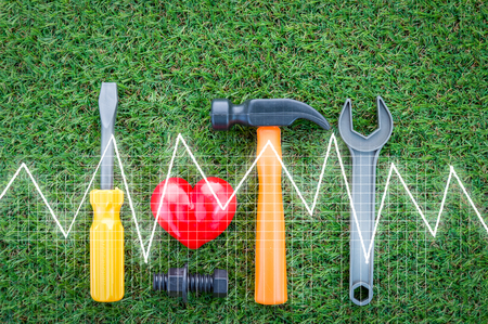 heart attack concept with red heart and tools with Heart cardiogram graph on green field.jpg
