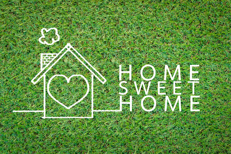 comfortable cozy: home sweet home drawing on grass field background.jpg Stock Photo