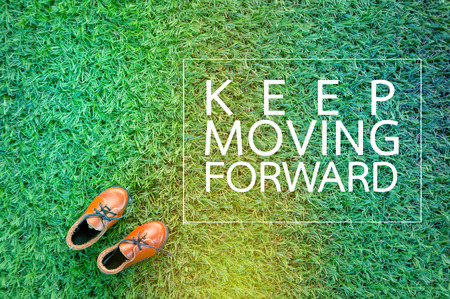 MOVING FORWARD concept with show on grass field texture.jpg Stock Photo