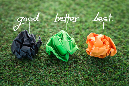 good better best: three colorful paper trash balls with good better best word on green grass texture background