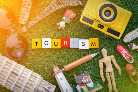 tourism concept with souvenirs around the world on green grass view from top.jpg