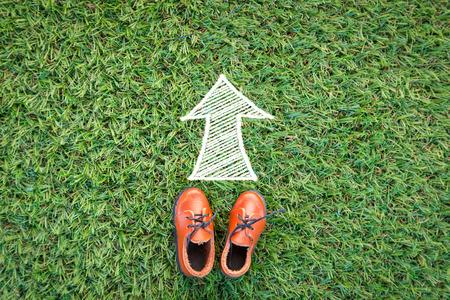 flechas direccion: juguete zapato de cuero en campo de hierba textura de fondo con el dibujo de la dirección de la flecha con espacio de copia