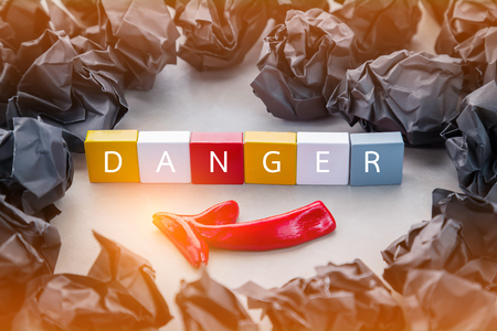 jitter: black crumpled paper ball and red arrow with plastic block with danger word inside on grey background Stock Photo