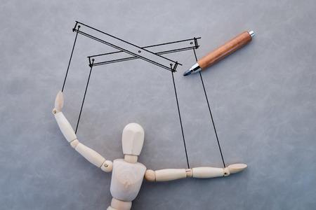 obedecer: concepto de negocio con la manipulaci�n de la figura de madera y dibujo sobre fondo gris Foto de archivo