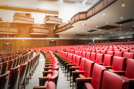 an old theater auditorium with red leather seats, interior