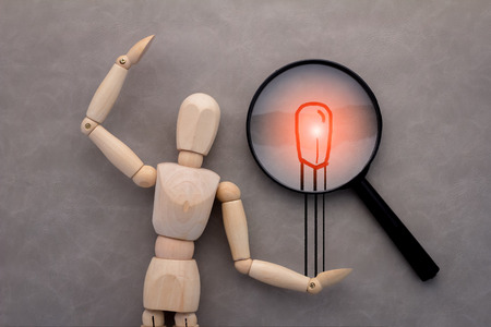 wooden figure: wooden figure and drawing of match and magnify on grey background.jpg