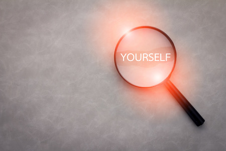 finding yourself concept with word and magnify on grey leather background.jpg Stock Photo