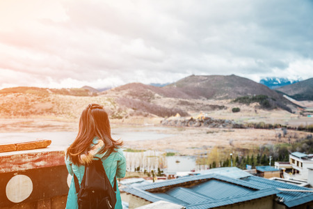 tibetian: girl tourist standing alone by the mountain  landscape during  summer vacation with his backpack back view Stock Photo