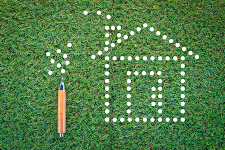 economize: eco house concept with paper dot and pencil on green grass texture background