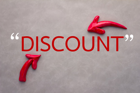 leather background: discount concept with red arrow on grey leather background