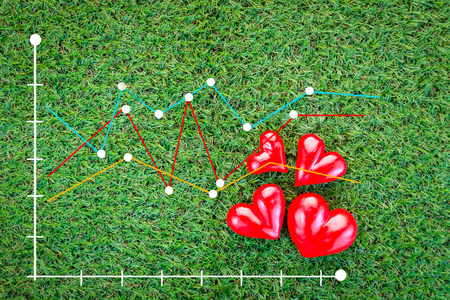 electrocardiograph: red heart on green field with beat graph analysis healthy concept Stock Photo