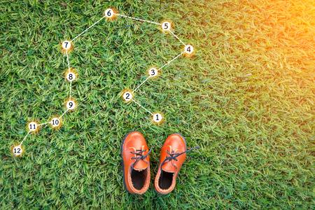 speelgoed lederen schoen op gras veld textuur achtergrond met punt en nummer