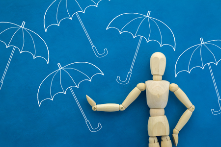 wooden figure: umbrella drawing with wooden figure on blue color background.jpg Stock Photo