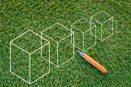 sharp pencil: sharp pencil and cube drawing on green grass  texture background with copy-space Stock Photo