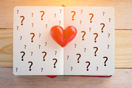 Book with opened pages and clay heart with question mark symbol love concept