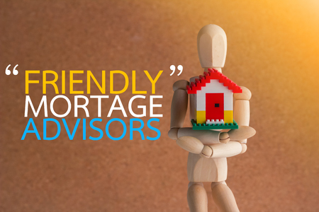 financial planning married: wooden man holding home model. Loan and montage concept