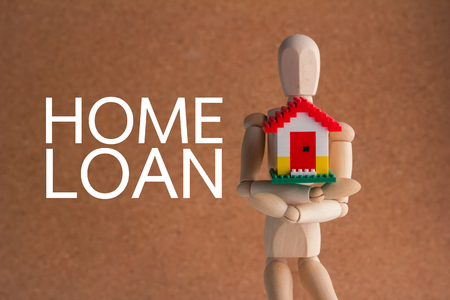 smilie: wooden man holding home model. Loan and montage concept