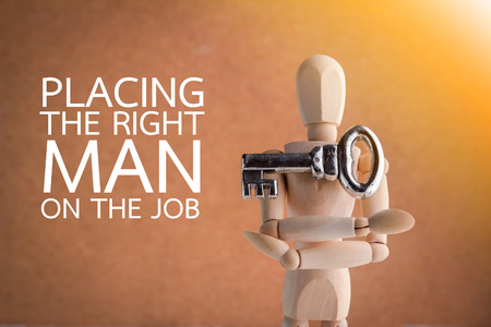 human character with a silver key in hand with brown background with concept right man right job