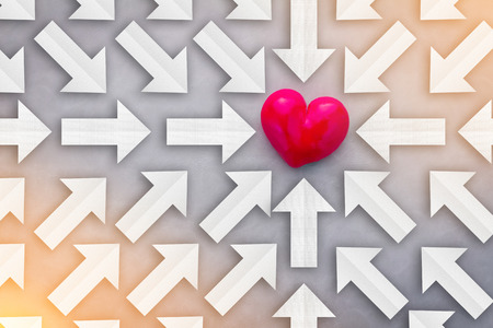 finding love: Finding Love concept with paper arrows point to red heart object on grey background.jpg Stock Photo