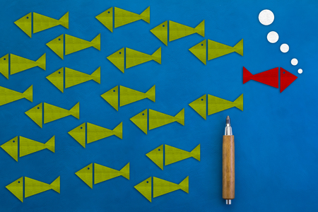risky: Being different, taking risky move for success in life concept fish paper cut with pencil on blue background
