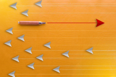 wooden pencil and red arrow leadership concept on yellow background