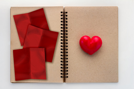 open your heart: Blank open notebook with red heart and red paper pad with copy space for your text Stock Photo