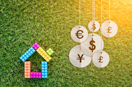 house model on grass texture with international money icon business concept.jpg Stock Photo