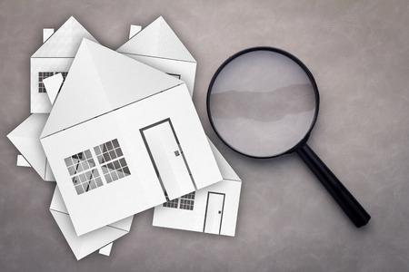 Papier Haus mit Vergrößerungsglas, Wohnungssuche auf grauem Hintergrund Standard-Bild