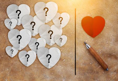 lápiz con el corazón rojo y blanco de papel con signo de interrogación en el interior el concepto de amor en la textura de color marrón background.jpg Foto de archivo