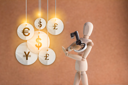 safekeeping: woden figure hold key with money symbol hanging business concept.jpg Stock Photo