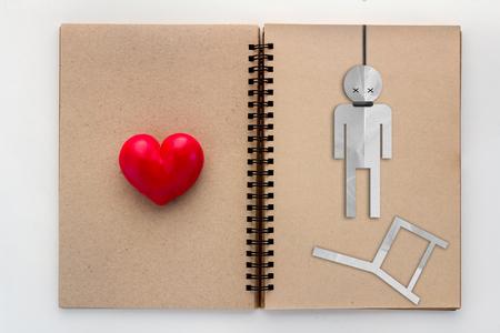 ahorcado: triste ahorcado descarne corazón rojo en la página en blanco reciclar el concepto de amor portátil Foto de archivo