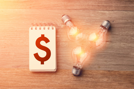 notebook with many light bulbs BUSINESS IDEAS ON WOODEN BACKGROUND.jpg Stock Photo