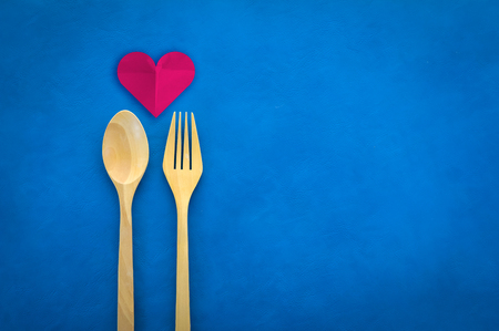 detrimental: Top view closeup beautiful Heart paper cut of love with wooden fork and spoon on blue leather board