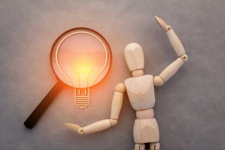 notifying: wooden man magnifying glass with light bulb paper cut shape on grey leather background creativity ideas concept