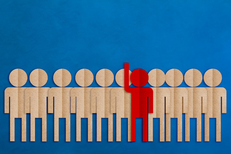 raise hand: red man paper cut raise hand among the others business leader concept on blue leather background.jpg Stock Photo