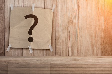 undetermined: recycle paper pad with question mark symbol on wooden background creativity ideas concept